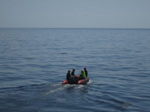 4 people in a zodiac with a drifter in the distance